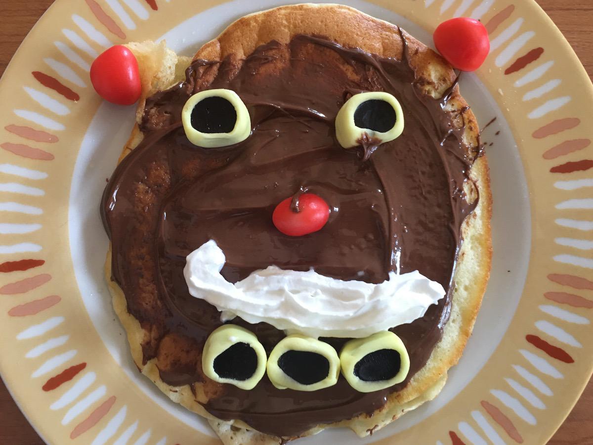 Il pancake di Greta rappresenta un viso. E' decorato con crema al cioccolato per colorare il volto. I baffi sono realizzati con la panna montata spray, gli occhi e la bocca con caramelle alla liquirizia, mentre naso e orecchie con caramelle rosse. Una ricetta davvero gustosa
